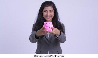 Young happy Persian businesswoman giving piggy bank - Studio...