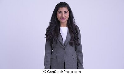 Young happy Persian businesswoman smiling - Studio shot of...