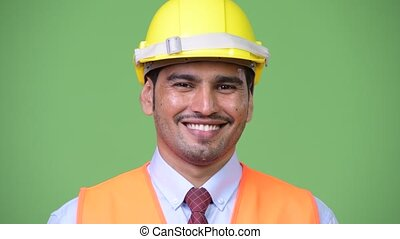 Young happy Persian man construction worker