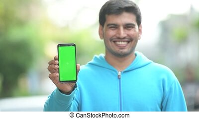 Young happy Persian man showing phone outdoors