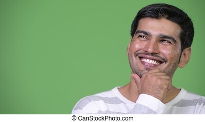 Young happy Persian man thinking