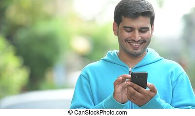 Young happy Persian man using phone outdoors