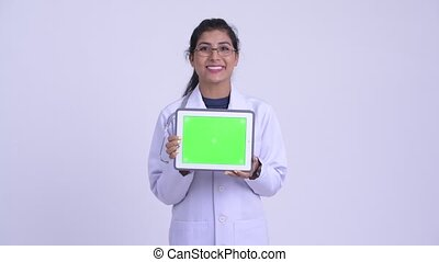Young happy Persian woman doctor showing digital tablet -...