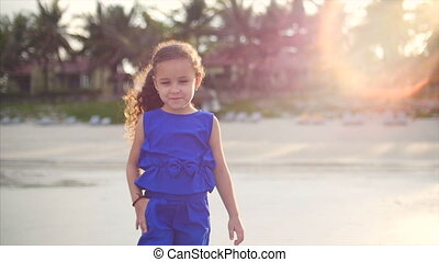 Young happy petite girl, walking near the ocean coast. Happy little girl in a blue suit, a Caucasian appearance, walking along the seashore.