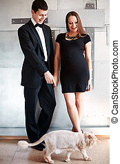 Young happy pregnant couple with their funny cat