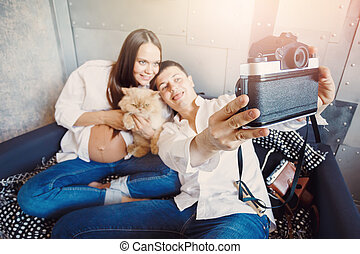 Young happy pregnant family have fun with old camera