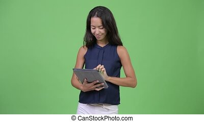 Young happy pregnant multi-ethnic businesswoman using...
