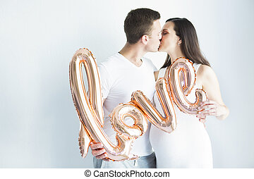 Young happy pregnant woman and man in love