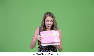 Young happy pregnant woman looking surprised while opening gift box