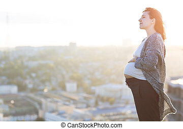 Young happy pregnant woman outdoor autumn day