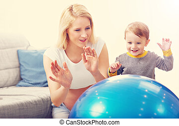 Young Happy Pregnant woman playing with son