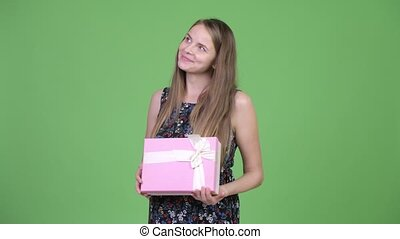 Young happy pregnant woman thinking while holding gift box