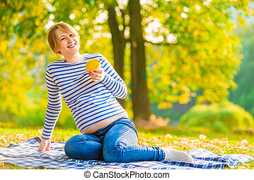 young happy pregnant woman with pear in the park