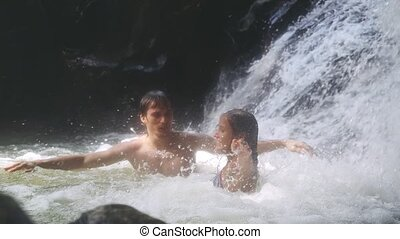 Young happy pretty couple relaxing under stream water in a tropical jungle by waterfall. Thailand. Koh Samui. slow motion. Travel concept. 1920x1080