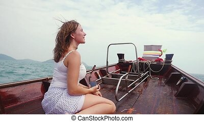 Young happy pretty woman takes pictures on the camera phone during a travel on a wooden boat, slow motion.