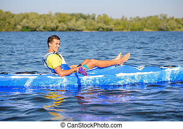 Young Happy Professional Kayaker Resting in Kayak on River under Bright Morning Sun. Sport and Active Lifestyle Concept