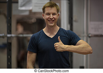 Young happy Scandinavian man giving thumbs up at the gym