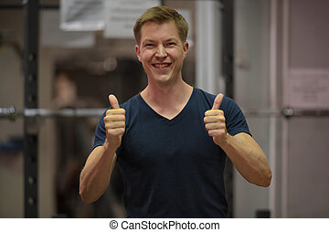 Young happy Scandinavian man smiling and giving thumbs up at the gym