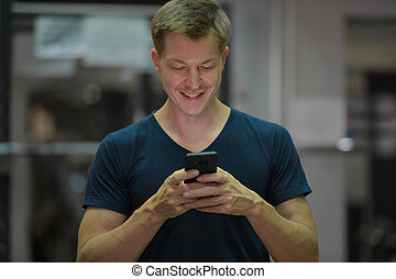 Young happy Scandinavian man using phone at the gym