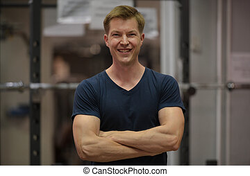 Young happy Scandinavian man with arms crossed at the gym