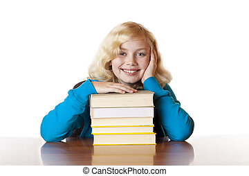 Young happy school girl sitting with books at desk