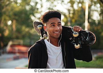 Young happy skateboarder man holding skateboard