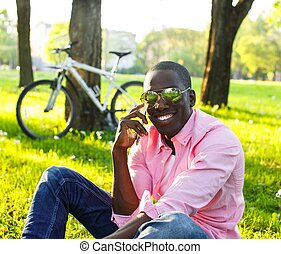 Young happy smiling african american with mobile phone and bicycle behind him in a park