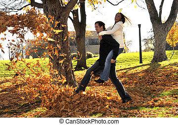 Young Happy Smiling Attractive Interracial Couple kicking yellow autumn leaves.