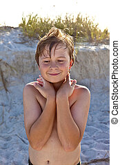 young happy smiling boy at the beach with wet hair after...