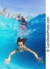 Young happy smiling child swimming underwater in the blue pool
