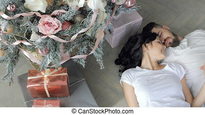 Young Happy Smiling Couple are Lying on the Floor near the Christmas tree