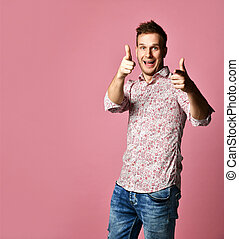 Young happy smiling man in shirt lucky winner pointing finger thumb up laughing shouting on pink