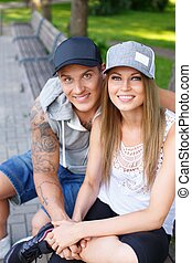 Young happy smiling sporty couple sitting on bench in a park