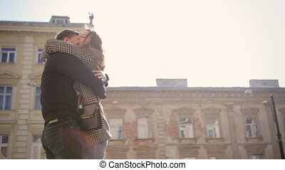 Young happy smiling woman hugging her boyfriend with all her love at the street.