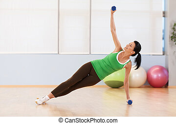 Young happy smiling woman in sportswear. girl doing fitness exercise on floor with dumbbell