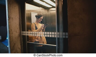 Young happy smiling woman riding elevator with transparent glass wall, walking out using smartphone shopping app online.