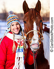 Young happy smiling woman with horse. Winter sport