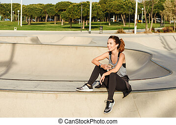 Young happy sports lady sitting outdoors in park