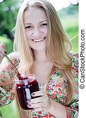 Young happy teen girl eating strawberry jam
