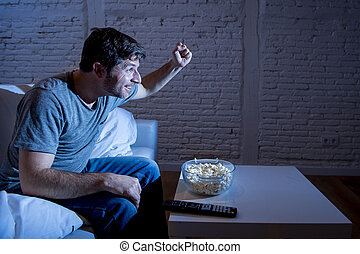 watching tv at night. young happy television addict man watching live sport match celebrating goal or victory tv at night