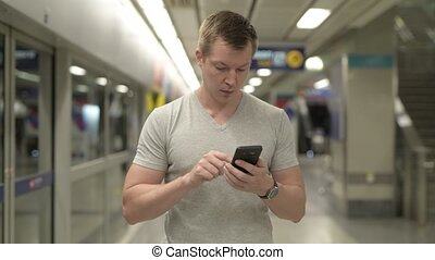 Young happy tourist man using phone at the underground train...