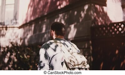 Young happy tourist with backpack walking slowly along sunny summer city street using smartphone social network app.