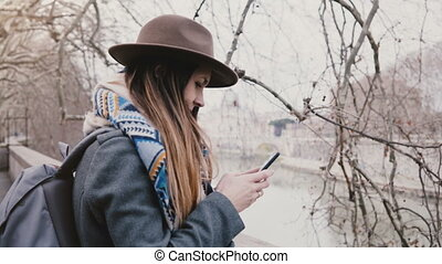 Young happy traveler girl with backpack taking smartphone...