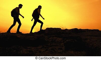 Young Happy Travelers Hiking with Backpacks on the Rocky Trail at Summer Sunset. Family Travel and Adventure Concept.