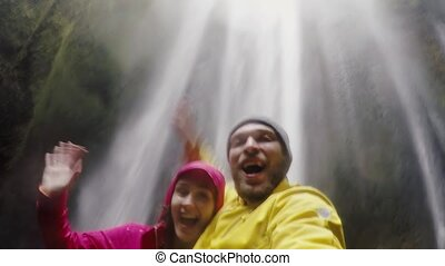 Young happy traveling couple taking a selfie on gopro camera. Man and woman near the Gljufrabui waterfall in Iceland.