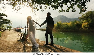 Young happy wedding couple walking together on the old quay in Montenegro, Budva with sea and mountains on background