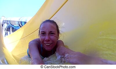 young happy white woman rides an open water slide, rolls over, laughs, selfie, slow motion