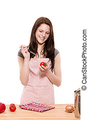 young happy woman about to cutting tomatoes on white background