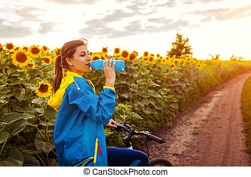 Young happy woman bicyclist drinking water after riding bicycle in sunflower field. Summer sport activity.