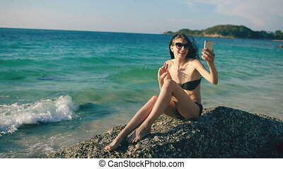 Young happy woman chatting with friends through internet using smartphone in ocean beach